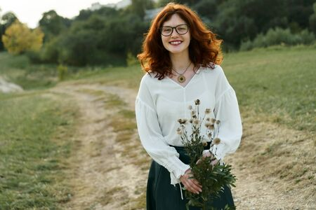 Beautiful young woman with red curly hair and freckles on her face in a white shirt. Close up portrait. Yellow-green summer background. Weekend in nature. Girl looking into the distance