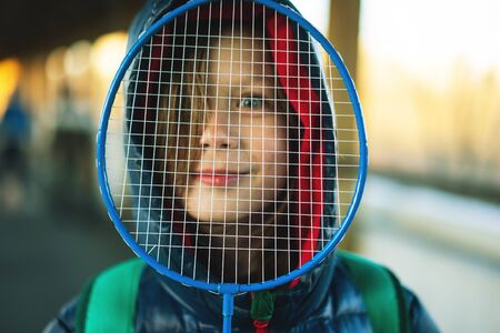 Boy looking through a badminton racket net. Weekend concept spring time sunset light. Family sport activities in vacation