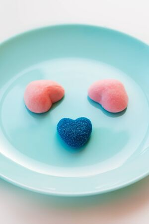 Marmalade and jelly candies sugar hearts blue and pink. Funny muzzle on a turquoise plate. Valentines classic Day Party Concept. Treats mint for guest children holiday birthday. Edible kids fun