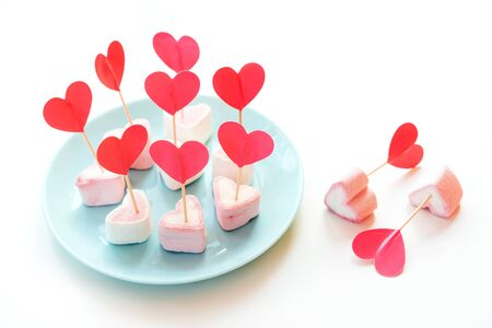 Marshmallows and paper hearts on skewers stuck in meringues standing on a blue turquoise mint plate. Valentines Day Party Neo Concept. Treats for guests on children birthday. Two hearts are separate