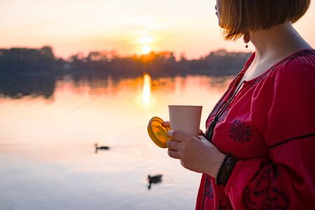 Short haired woman is walking in the park near the river and holding a bamboo cup silicone lid with hot coffee in her hand. Fashionable summer clothes. Beautiful sunset and ducks floating in the pond