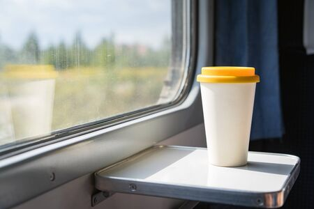 A bamboo coffee cup with a yellow silicon lid. Coffee to go on a table in the train overlooking a beautiful rural green landscape. Travel, lifestyle. Concept zero waste, reusable recyclable dishes