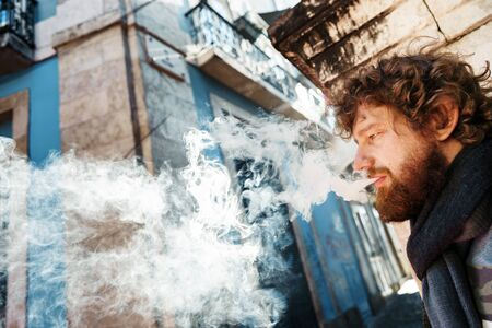 Bearded man with curly hair smoking through a veil of smoke. Unhealthy addiction concept . Retreat at old Europe town street Portugal. Selective focus 免版税图像 - 140204307