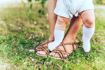 Female and childrens legs in summer sandals on the green grass. Mom and her six months old daughter learn to walk. First steps