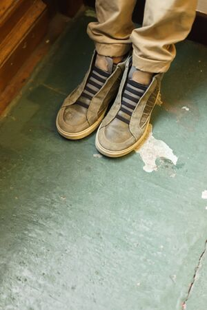 The legs of a boy in khaki pants and sneakers standing on a green painted floor at the door of the room. The concept of minimalism composition, faceless, vertical format. Impersonal.