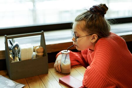 Girl teenager sitting in cafe at a table in red knitted sweater waiting and drinking cocktail through a straw. Milk chocolate cocktail in a glass reusable bottle with a foil cap and a disposable tube