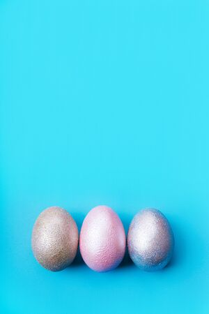 Three colored chicken eggs of pink, silver, golden and blue color on a light blue pastel background. Minimalistic creative classic easter festive vertical flat lay. Copy space for text Stockfoto