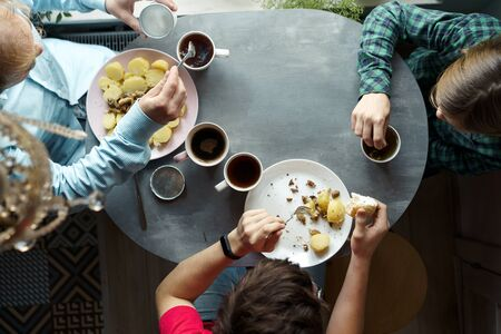 Family breakfast at the oval table by the window. Father and two sons eating potatoes and drinking coffee from white ceramic mugs. Top view through a crystal chandelier. Weekend Family Customs Concept Stockfoto