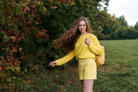 Cheerful smiling teenage girl of 14 years old with long curly red hair in a yellow sweater and with a backpack on the nature. Summer vacation weekend concept