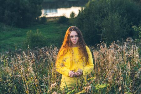 Cheerful smiling teenage girl of 14 years old with long curly red hair in a yellow sweater on the nature. Summer vacation weekend concept. Selective focus Stockfoto