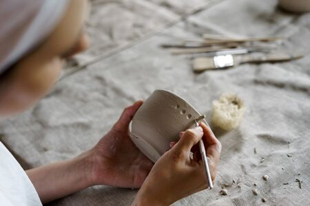 Female hands hold a bowl for casting clay products. Shaped method for making clay dishes. Handwork. Pottery making