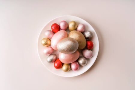 Colored painted pearl chicken and quail eggs of pink, red, silver, golden color on a purple plate pastel background. Minimalistic creative idea easter festive flat lay. Copy space for text Stockfoto