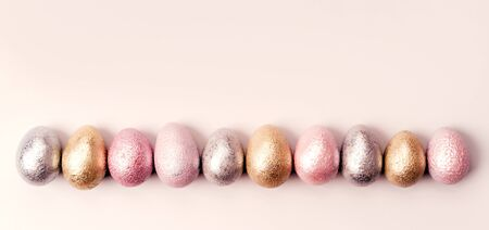 Colored painted pearl chicken and quail eggs of pink, silver, golden color on pastel background. Minimalistic creative idea easter festive flat lay banner. Copyspace for text Stockfoto