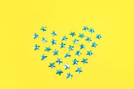 Creative festive sky blue heart from stars on a yellow background. Flat lay