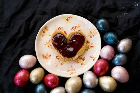 Colored painted pearl quail eggs of pink, silver, golden and blue color on black handmade ceramic plate background. Homemade heart shaped pastries jam. Easter festive flat lay. Low key photo
