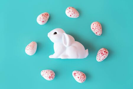 White toy neon rabbit with eggs candy on Neo mint background . Festive easter layout. Minimal Creative Idea Concept. Family holiday. Baby kids fun