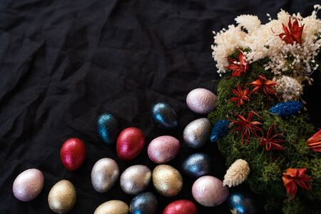 Colored painted pearl quail eggs of pink, silver, golden and blue color on black handmade easter wreath background. Homemade layout. Easter festive flat lay. Low key photo