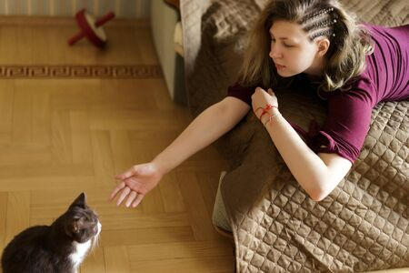 A woman and a small black and white british kitten are lying on the sofa. Calm and Relax