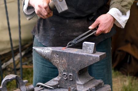 medieval blacksmith: Blacksmith working on metal medieval fire iron hammer work