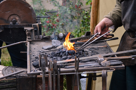red hot iron: Blacksmith working on metal medieval fire iron hammer work