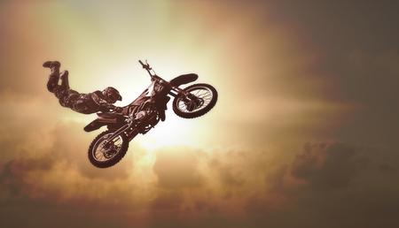 Extremsporthintergrund - Schattenbild des Radfahrers springend auf Motorrad auf Sonnenuntergangbremsung Standard-Bild
