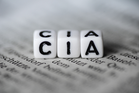 Word CIA formed by wood alphabet blocks on newspaper Stock Photo