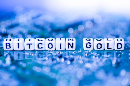 Word BITCOIN GOLD formed by alphabet blocks on mother cryptocurrency