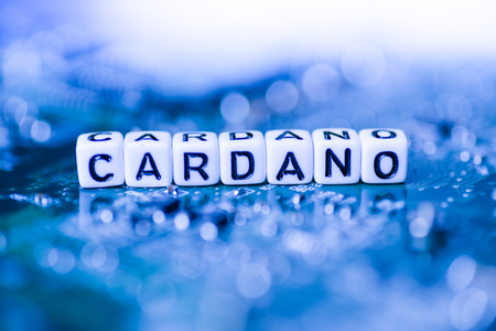 Word CARDANO formed by alphabet blocks on mother cryptocurrency Stock Photo