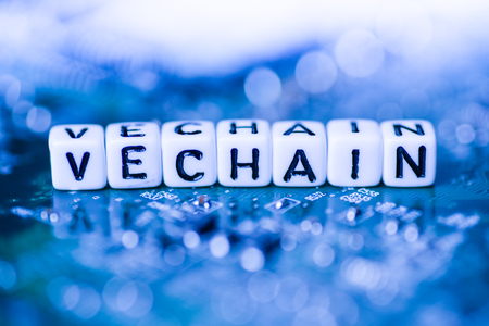 Word VECHAIN formed by alphabet blocks on mother cryptocurrency Stock Photo
