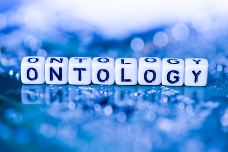 Word ONTOLOGY formed by alphabet blocks on mother cryptocurrency Stock Photo