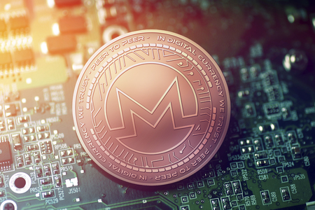 shiny copper MONERO cryptocurrency coin on blurry motherboard background Stock Photo