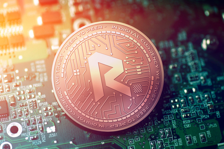 shiny copper REVAIN cryptocurrency coin on blurry motherboard background