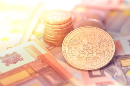 shiny golden ATLANT cryptocurrency coin on blurry background with euro money
