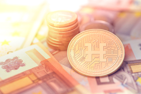 shiny golden HDAC cryptocurrency coin on blurry background with euro money