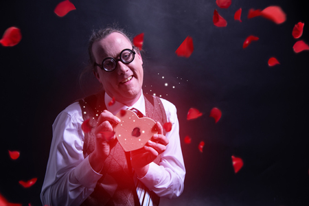 Crazy happy guy holding red heart gift box - present valentines day - love - with flying petals - roses Banco de Imagens