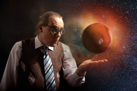 Funny scientist looking to universe and planet mars Stock Photo