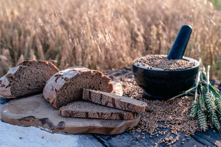bread flour and corn on a old table with cornfield in the background 免版税图像 - 126604342