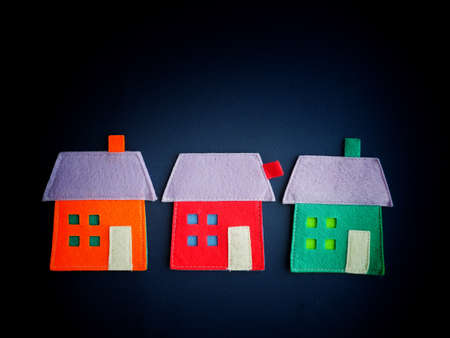 investment concept: Three colorful textile houses on blue background Stock Photo