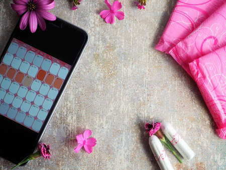 Woman hygiene protection during menstruation. Close up cotton tampons, pink menstruation pads, pink flowers and mobile phone with menstruation calendar on vintage table.