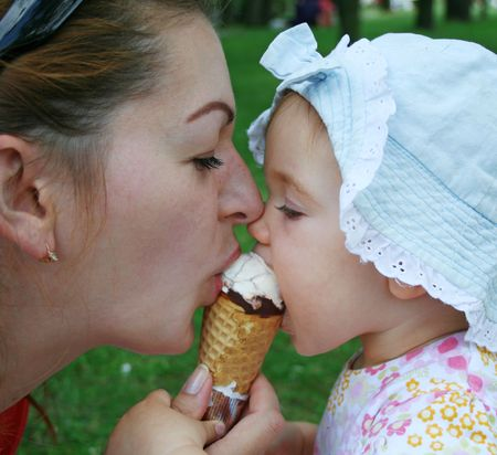 A mother is sharing an icecream with her daughter. photo