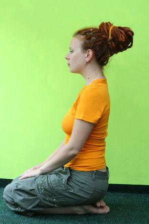 pierced ears: An orange girl on a green background. Stock Photo