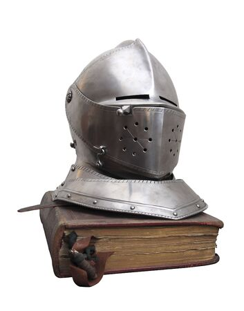 A knights helmet on an old book. Stock Photo