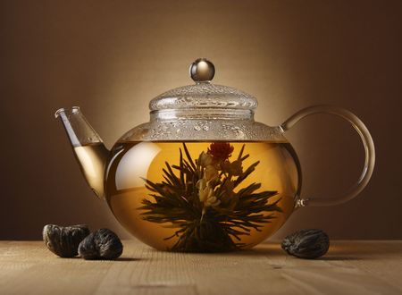 A glass teapot with Lotus Flower Chinese tea. photo