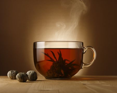 A glass bowl with hot Chinese tea.