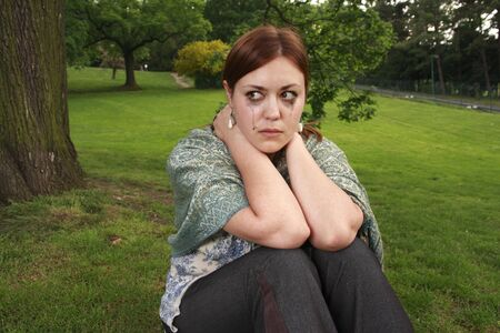 A girl in tears. Facial emotions of a young woman sitting alone in a garden. Stock Photo - 3066010
