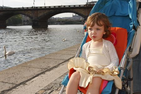 A little girl is sitting in a carriage on a river embankment and watching the swans. photo