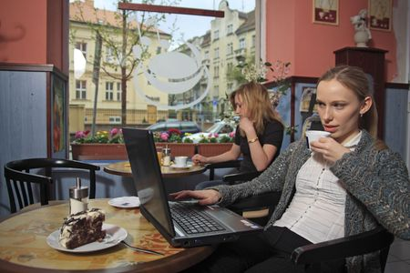 Two girls are sitting in a cafe, waiting, drinking coffee, working with a laptop. photo