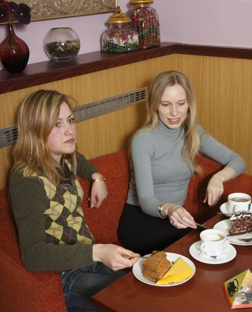 Two girls are sitting in a cafe, drinking coffee. photo