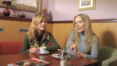 Two girls are sitting in a cafe, talking, drinking coffee. photo