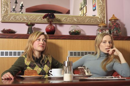 Two girls are sitting in a cafe, talking, thinking. photo